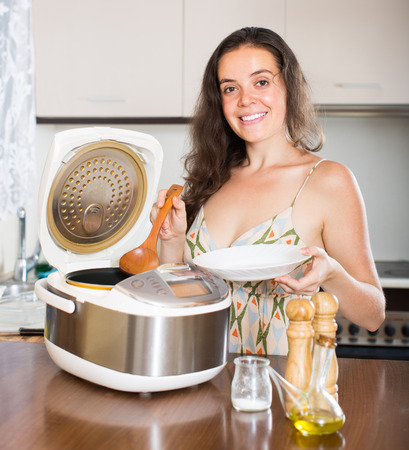 slow cooker: Young housewife cooking with new multicooker in home interior Stock Photo