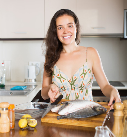 gilthead bream: Happy girl holding raw fish at home kitchen Stock Photo