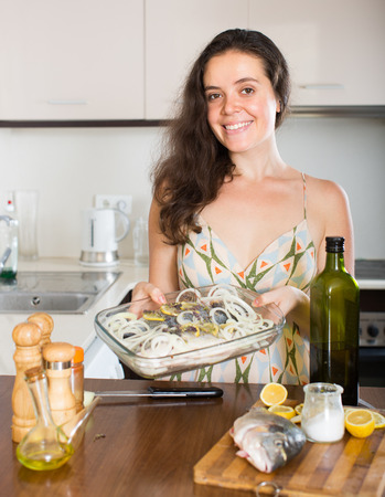 panful: Happy girl with raw fish on frying pan at home kitchen