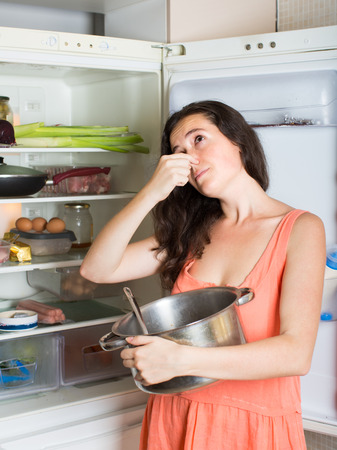 frowy: cheerful  woman  holding her nose because of bad smell near fridge at home