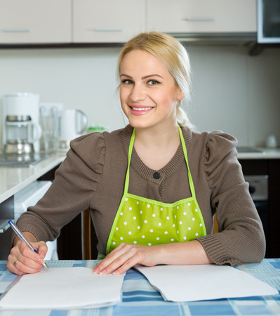 contractual: Happy woman at kitchen signing contractual agreement for renting new flat