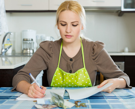 financial problems: Sad  young woman thinking about the financial problems  at home Stock Photo