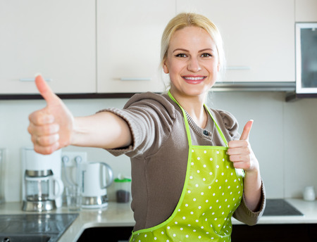 staying: Cheerful blonde girl staying at kitchen and showing thumbs up