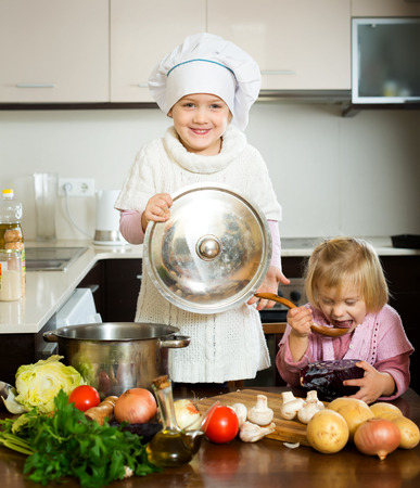 cover girls: Little girls learning how to cook in the kitchen. One girl is holding a cover of a pan and the other is tasting something from a spoon Stock Photo