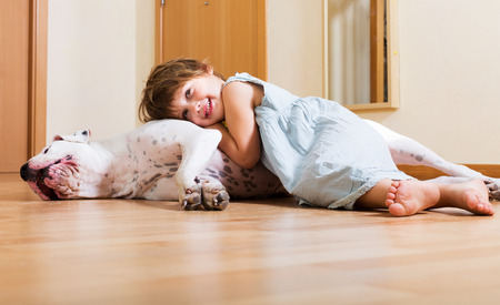 Cheerful smiling little girl hugging big white dog at home