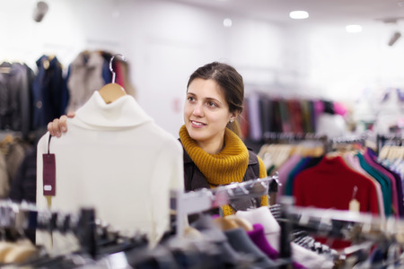 'pull over': Smiling girl choosing  sweater at clothing shop
