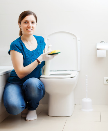 Smiling girl in blue cleaning in bathroom at home photo