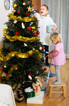 five years old: Little girls around three of five years old decorating a christmas tree