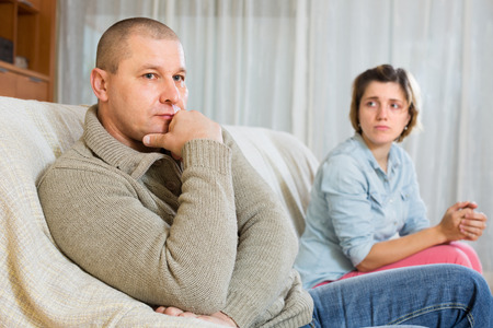 russian man: Couple quarrel at home. Sad ordinary man against unhappy woman