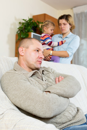 grievance: Family quarrel. Sadness man against and crying woman at home Stock Photo