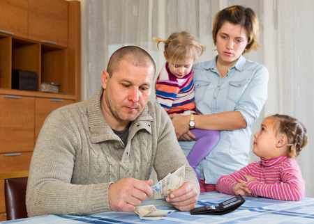 avidity: Financial problems in family. Sad woman wit children against husband at home with money