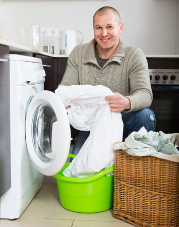 man laundry: Home laundry. Smiling man using washing machine in kitchen at home