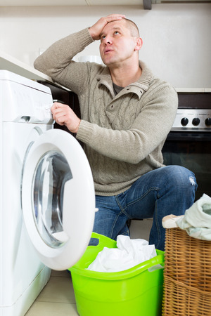 unsatisfactory: Home laundry. Sad adult guy using washing machine at home