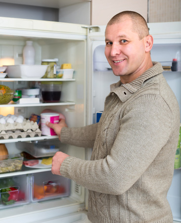 starving: Man indoors taking food from refrigerator