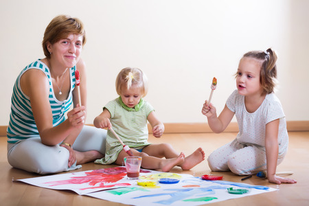 Happy mother and children painting with paint  on floor photo