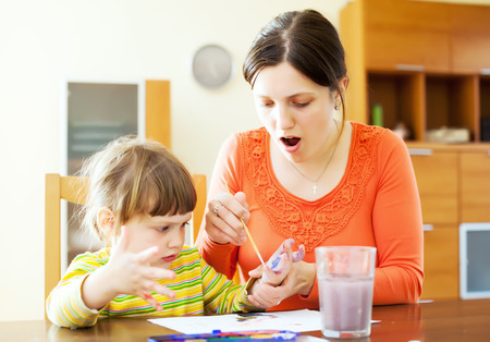 handbreadth: Happy mother and baby  plays with watercolor in home interior. Focus on woman only