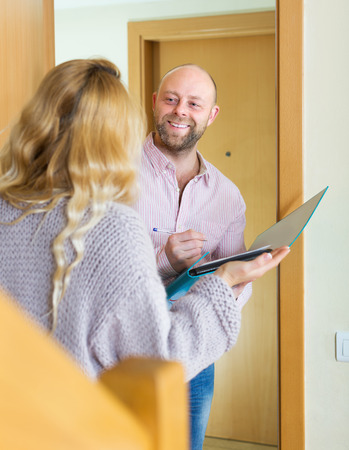 outreach: Woman answer questions of outreach worker with paper in home door Stock Photo