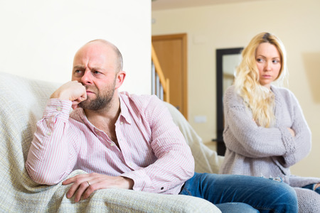 Portrait of a couple on a couch indoors after a quarrel. Sad husband sitting turned away from his wife that is looking at him in disappointment