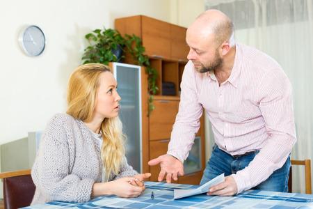 problemas familiares: Familia una esposa y un marido argumentando sobre el relleno en algunos documentos y formularios financieros Foto de archivo