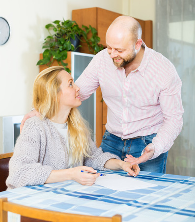 Positive couple discussing details of marriage settlement at home photo