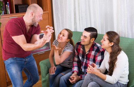 booze: Cheerful group of young adults having fun at house booze party Stock Photo