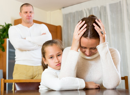 daughter gives solace to crying mother  at home and angry father photo