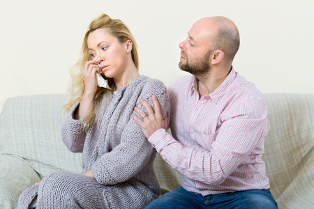 fracas: Man tries reconcile with crying woman after conflict at home. Focus on girl Stock Photo