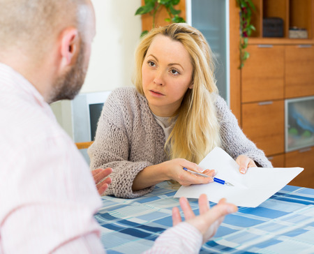 covetous: Quarrel in young family over financial documents at the table at home Stock Photo