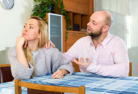appease: Man asking for forgiveness from sad woman at home Stock Photo
