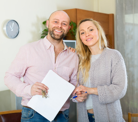 hypothec: Happy smiling young married couple with contract for buying apartment and keys
