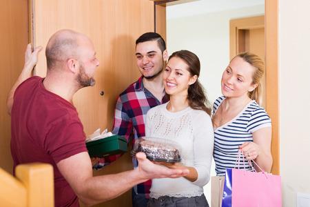 acogida: El hombre da la bienvenida a los amigos sonrientes en casa Foto de archivo