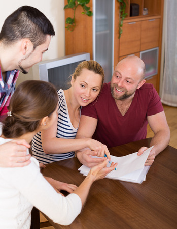 spouses: Young spouses sitting with documents and asking happy friends for advice