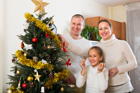 Smiling parents and daughter decorating Christmas tree in the living room at home