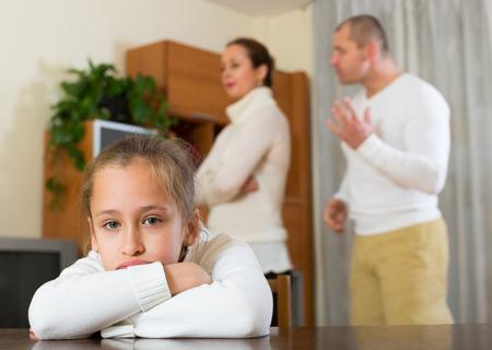 fracas: Sad daughter and parents having quarrel at home. Focus on girl