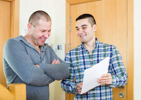lodger: Adult lodger meeting neighbor with papers at doorway. Focus on the right man Stock Photo