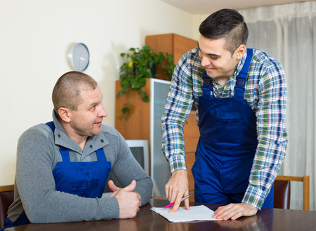 collaborator: Two male workers in uniform reading contents of order at office Stock Photo