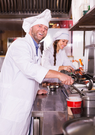 chafe: Cheerful happy cooks greeting customers at bistro kitchen and smiling Stock Photo