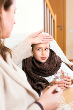 schooler: Loving mother checking her ill daughters temperature