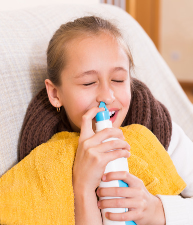 catarrh: Small girl easily using aqua del mar spray indoor Stock Photo