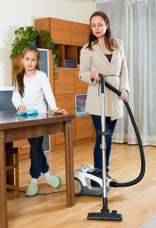 Woman with vacuum cleaner and smiling daughter with a rag at the home photo