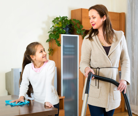 Mother and daughter are cleaning the house. Mom is vacuuming the floor and girl is wiping of dust from the table photo