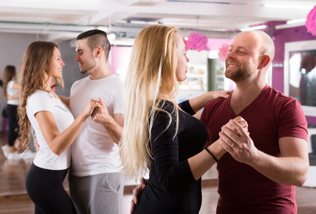 a pair of: Group of positive smiling young adults dancing salsa at dance class