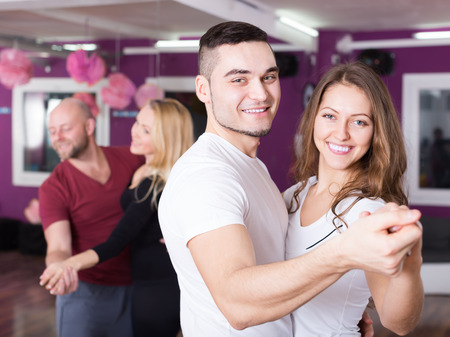 Group of smiling positive young adults dancing at dance class. Focus on guy Stock Photo