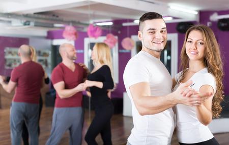 Gruppe der lächelnden jungen Erwachsenen tanzen Salsa-Tanzkurs an. Konzentrieren Sie sich auf guy Standard-Bild - 37566039