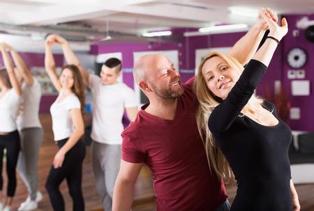 pareja bailando: Parejas sonrientes que disfrutan de la danza asociado: piscina cubierta