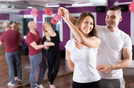 danza: Dos parejas de jóvenes sonrientes que tienen clase de baile en el club Foto de archivo