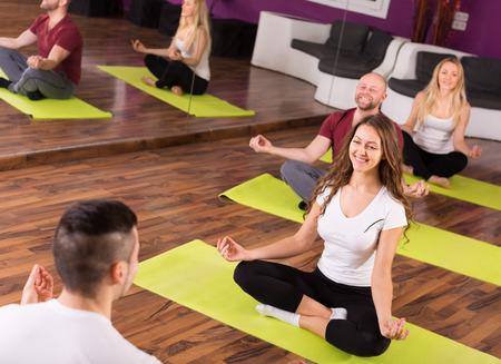 adult learners: entrenador europeo que muestra a estudiantes adultos nueva postura de yoga en clase
