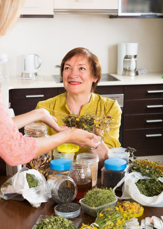 dried herbs: Smiling mature woman with adult daughter with dried herbs