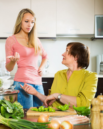 talkative: Mature female with sad adult daughter sharing bad news in kitchen