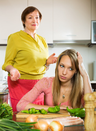 fracas: Adult daughter and mother after quarrel  in home kitchen